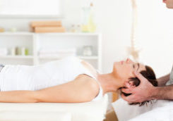 Chiropractor stretching a cute woman in a room